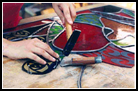 Lisa Maywood - stained glass artist working on a custom piece of glass art
